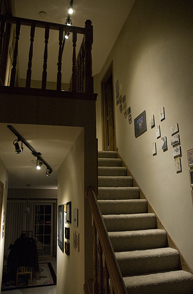 This stair and hall are lighted with generic PAR20 and PAR30 LED retrofit lamps. The total energy consumed for the space shown is 36 watts.